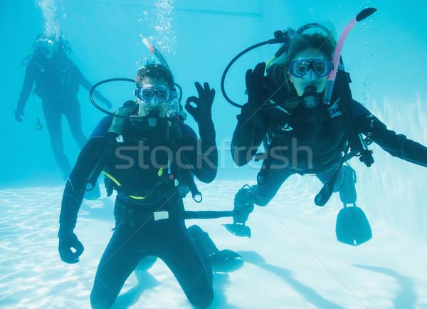 Friends on scuba training submerged in swimming pool two looking Stock photo © wavebreak_media