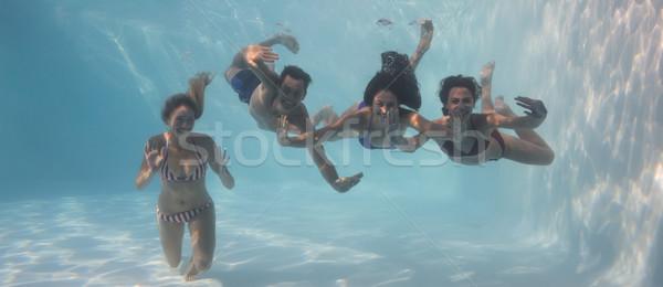 Mosolyog barátok néz kamera vízalatti úszómedence Stock fotó © wavebreak_media