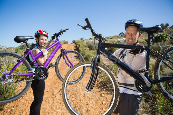Active couple carrying their bikes on country terrain together Stock photo © wavebreak_media