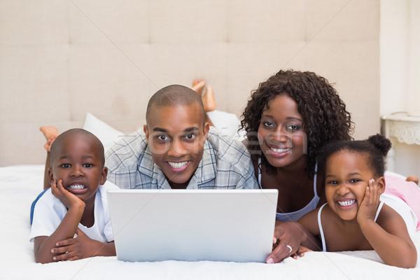 счастливая семья используя ноутбук вместе кровать домой спальня Сток-фото © wavebreak_media