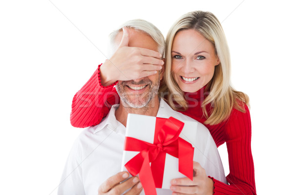 Smiling woman covering partners eyes and holding gift Stock photo © wavebreak_media