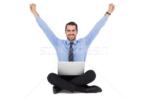 Smiling businessman sitting on the floor cheering Stock photo © wavebreak_media