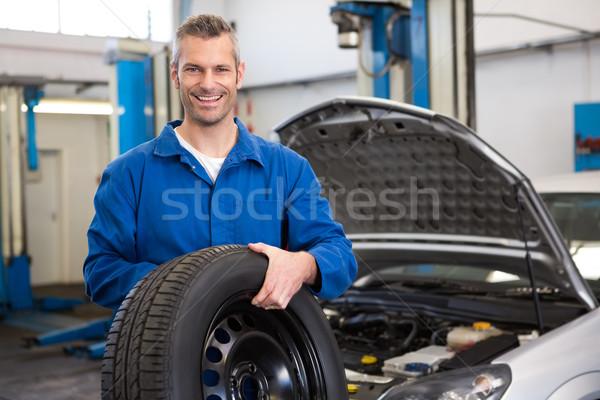 Mechanic holding a tire wheel Stock photo © wavebreak_media