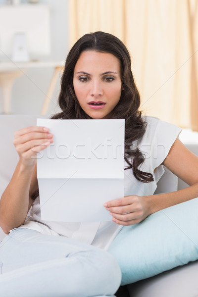 Shocked brunette reading letter on couch Stock photo © wavebreak_media