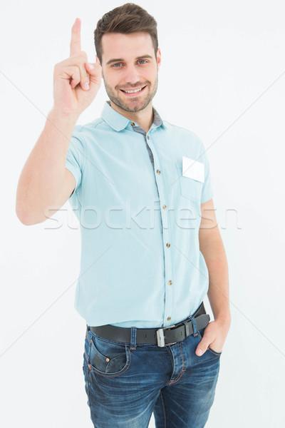 Delivery man pointing upward on white background Stock photo © wavebreak_media