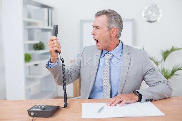 Irritated businessman answering phone  Stock photo © wavebreak_media