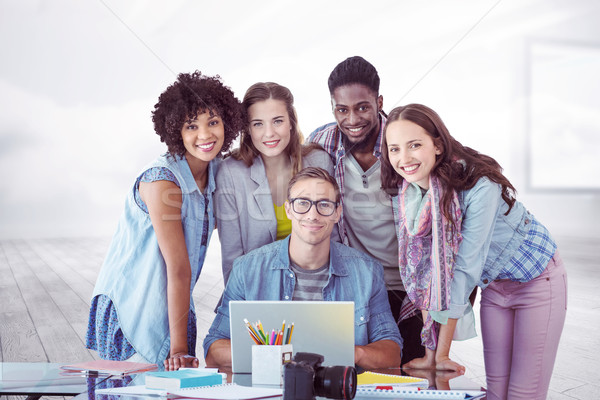 Stock photo: Composite image of fashion students working as a team