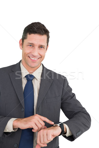 Businessman using his smart watch and smiling at camera Stock photo © wavebreak_media
