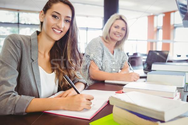 Smiling matures females students writing notes at desk Stock photo © wavebreak_media