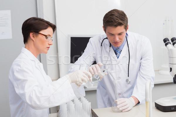 Tudósok áramló vegyi folyadék tölcsér laboratórium Stock fotó © wavebreak_media