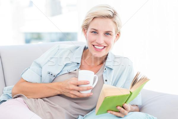 Csinos szőke nő olvas könyv tart bögre Stock fotó © wavebreak_media