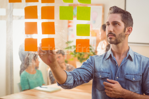 Concentrated businessman looking post its on the wall Stock photo © wavebreak_media