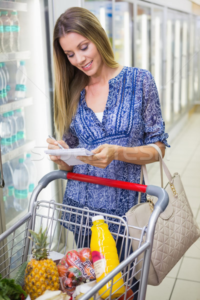 Woman writing in his notepad in the frozen aisle  Stock photo © wavebreak_media