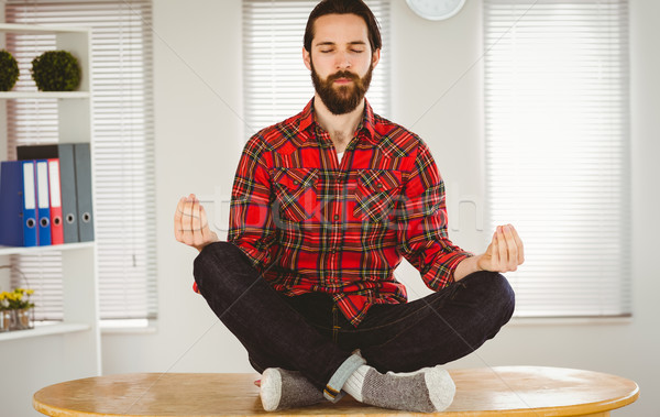 Hipster businessman meditating at his desk Stock photo © wavebreak_media