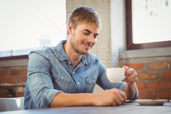 Handsome man smiling and drinking coffee Stock photo © wavebreak_media