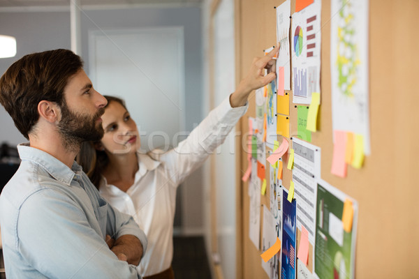 Young businessman with female colleague analyzing charts at office Stock photo © wavebreak_media