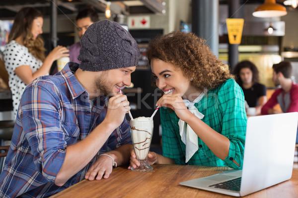 Happy couple looking at each other while having milkshake Stock photo © wavebreak_media