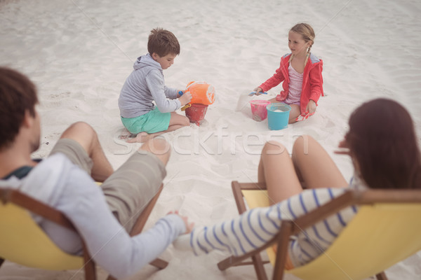 Siblings playing by parents relaxing on launge chairs at beach Stock photo © wavebreak_media