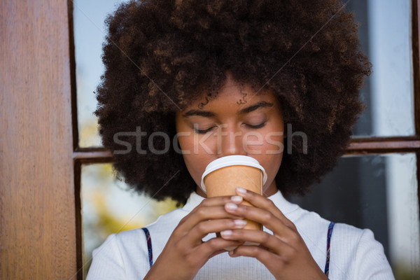 Close up of woman drinking coffee against door Stock photo © wavebreak_media