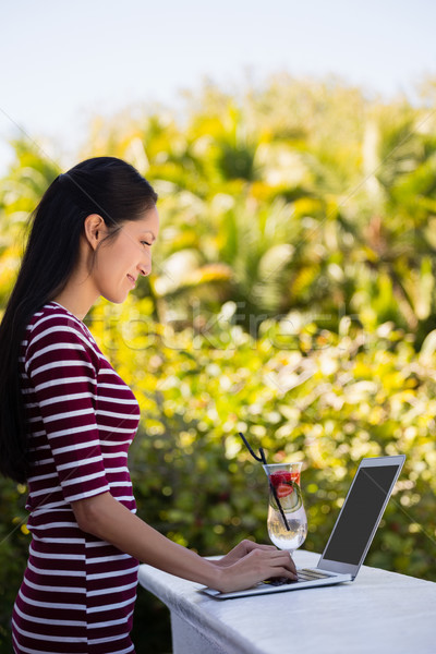 Young woman using laptop on retaining wall at restaurant Stock photo © wavebreak_media