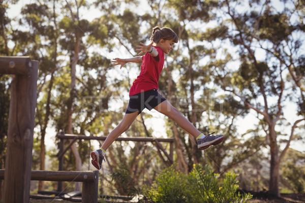 Determinado nina saltar obstáculo arranque campamento Foto stock © wavebreak_media