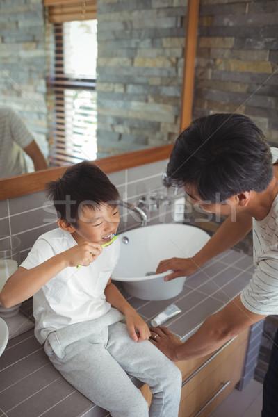 Son brushing his teeth with father in bathroom Stock photo © wavebreak_media