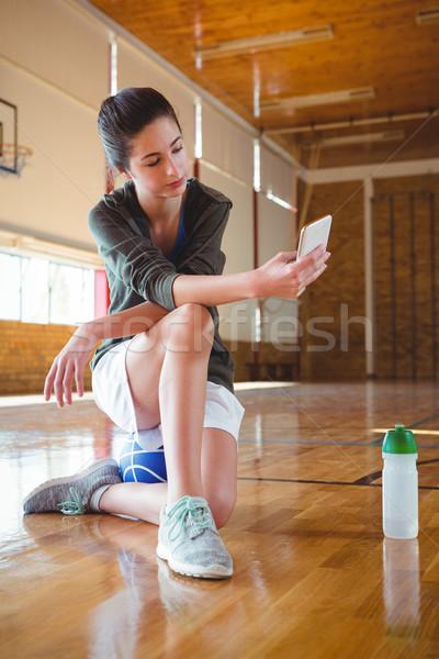 Weiblichen Handy Sitzung Basketballplatz Stock foto © wavebreak_media