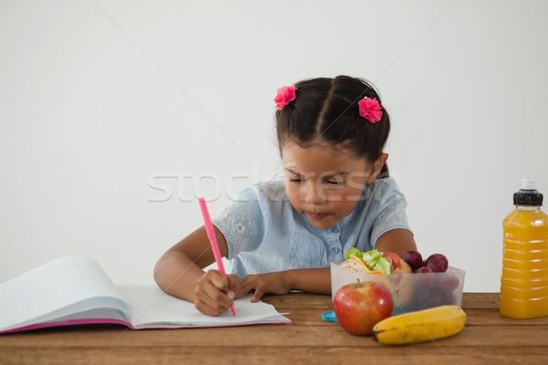 Schoolgirl doing her homework against white background Stock photo © wavebreak_media