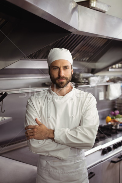 Stock photo: Portrait of confident chef standing with arms crossed in commercial kitchen
