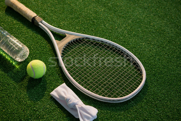 High angle view of tennis ball with racket and napkin by water bottle Stock photo © wavebreak_media