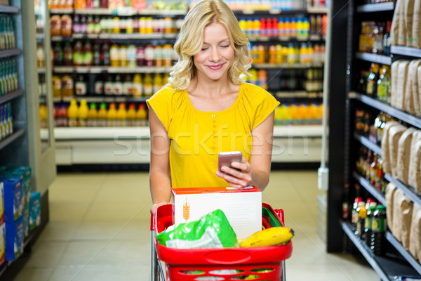 Smiling woman with smartphone pushing trolley in aisle Stock photo © wavebreak_media