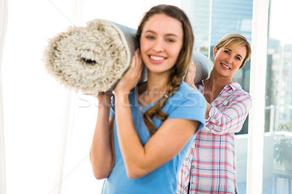 Stock photo: Mother and daughter holding a carpet