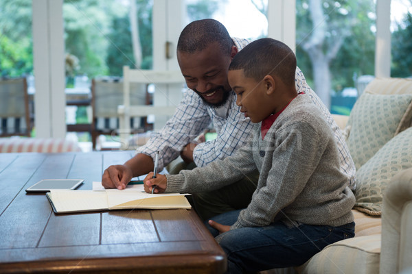 Father helping his son with homework in living room Stock photo © wavebreak_media