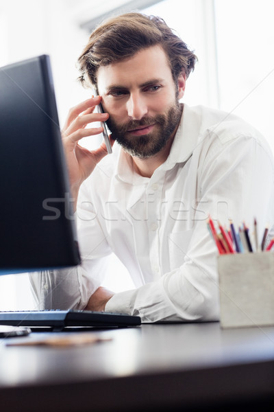 A man passing a call in front of this desk  at the office Stock photo © wavebreak_media