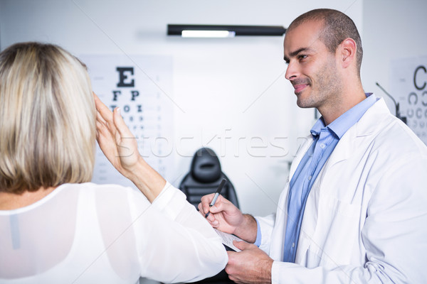 Male optometrist taking eye test of female patient Stock photo © wavebreak_media