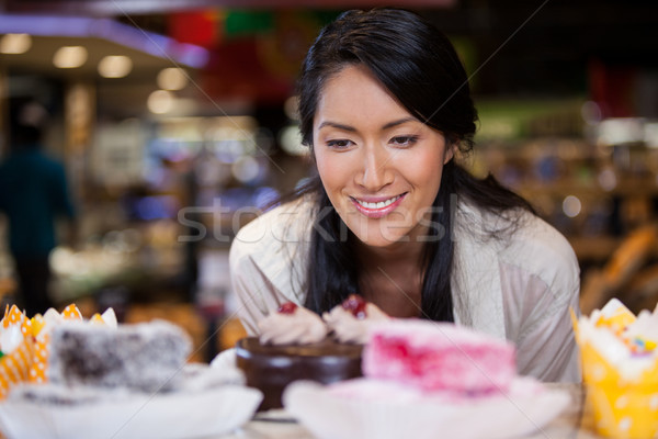 Happy woman selecting desserts from display Stock photo © wavebreak_media