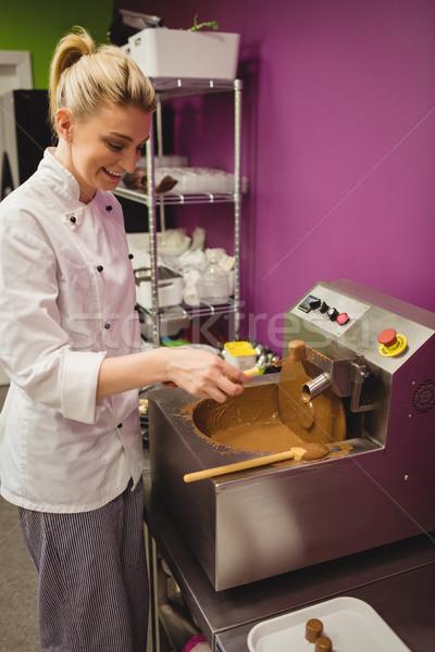 Worker dipping marshmallow in chocolate blending machine Stock photo © wavebreak_media