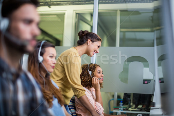 Female customer service executive interacting with her colleague at desk Stock photo © wavebreak_media