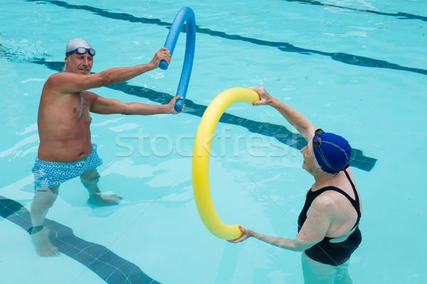 Senior couple exercising with pool noodle Stock photo © wavebreak_media