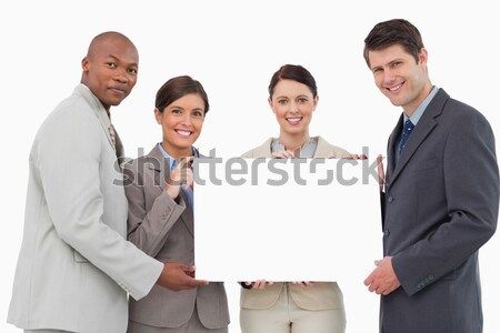 Stock photo: Multi-ethnic business people holding a white card