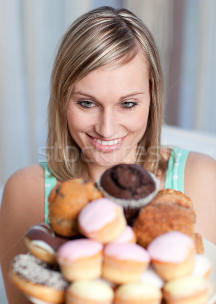 Stock photo: Charming woman holding a plate of cakes