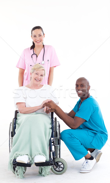 Doctors with a patient in a wheel chair smiling at the camera Stock photo © wavebreak_media