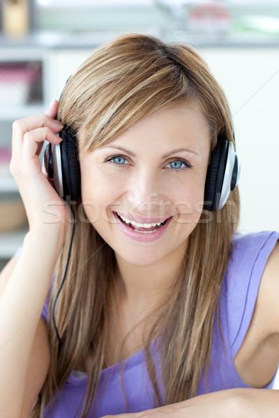 Delighted woman using headphone in the kitchen Stock photo © wavebreak_media