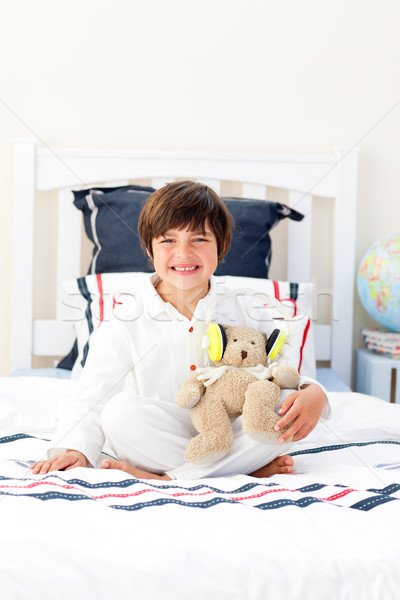 Smiling little boy playing with a teddy bear in his bedroom Stock photo © wavebreak_media