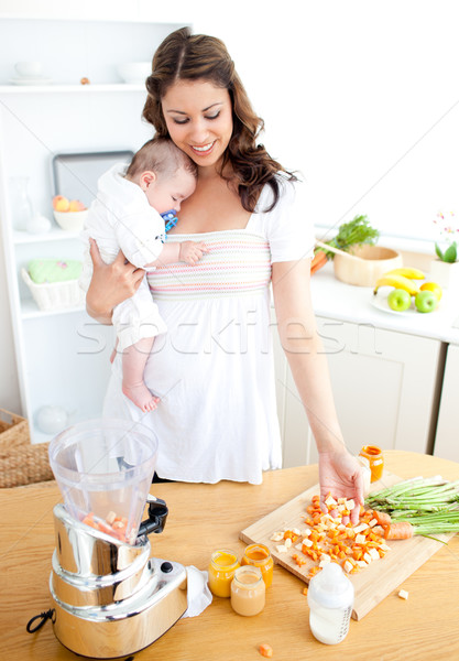 Caring young mother preparing vegetables for her baby in the kitchen at home Stock photo © wavebreak_media