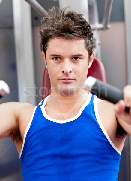 Confident young man using a bench press in a fitness center Stock photo © wavebreak_media