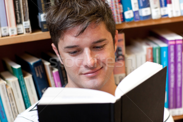 Portrait of a smiling male student reading a book sitting on the floor in a bookshop Stock photo © wavebreak_media