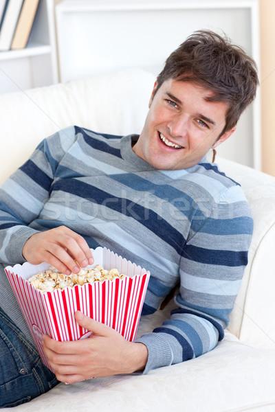 Elragadtatott fiatalember eszik pattogatott kukorica kanapé otthon Stock fotó © wavebreak_media