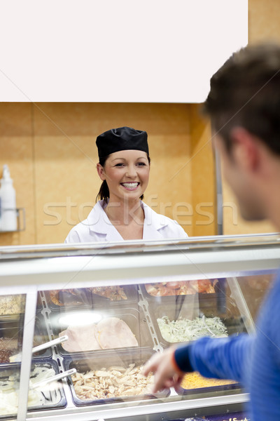 Handsome student showing his choise to the cook in the cafeteria of his campus Stock photo © wavebreak_media