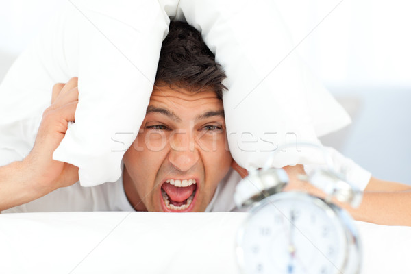 Stock photo: Angry man putting his head under the pillow while his alarm clock ringing